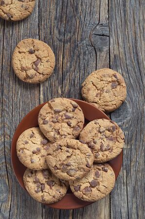 Yummy chocolate chips cookies in plate on old wooden table, top view