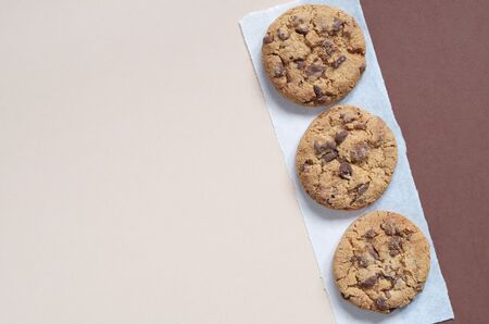 Three chocolate chip cookies on two-color background, top view with copy space Reklamní fotografie