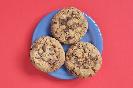 Chocolate chip cookies on a blue plate on a red background, top view