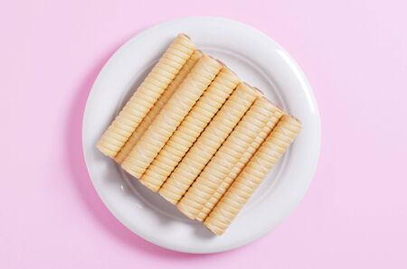 Creamy wafer rolls in plate on a pink background, top view