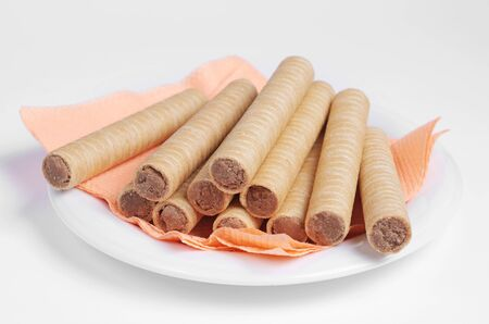 Wafer rolls with chocolate in a plate with a pink napkin on white background. Selective focus Stok Fotoğraf