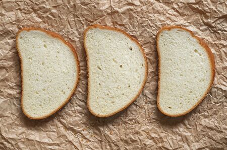 Three slices of bread on crumpled paper close up, top view