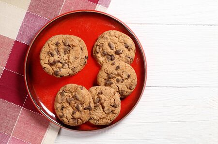Chocolate chip cookies on a red plate on white wooden table, top view. Copy space