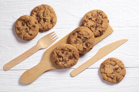 Chocolate chip cookies, wooden fork and knife on white table Stock Photo