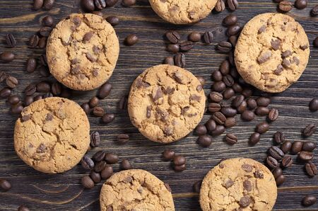 Chocolate chip cookies and coffee beans on old wooden table, top view. Food background