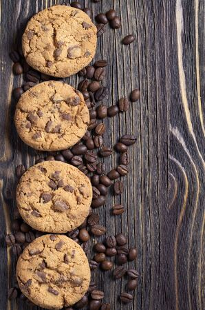 Chocolate chip cookies and coffee beans on old wooden table, top view with copy space