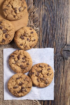 Chocolate chip cookies on old wooden table, top view Stock Photo