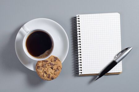 Notepad with pen, coffee and chocolate chip cookies on gray desk, top view