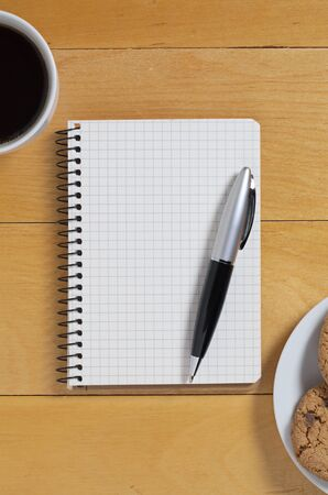 Open notepad, pen and cup of coffee with chocolate chip cookies on wooden desk, top view
