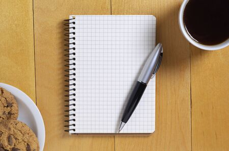 Notepad, pen and coffee with chocolate chip cookies on wooden desk, top view