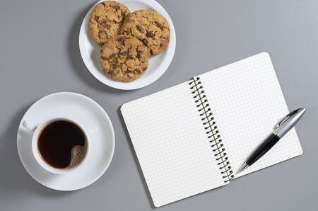 Coffee, chocolate chip cookies and notepad with pen on gray desk, top view