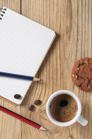 Notebook, pencils and coffee with cookies on wooden table, top view