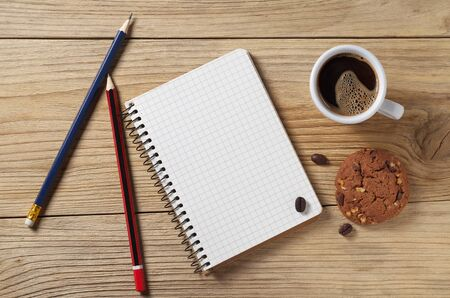Blank notepad background and coffee with chocolate chip cookie. Top view