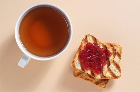 Stack of toasted bread with jam and cup of tea on a beige background, top view