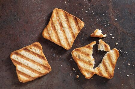 Small grilled toasted bread on a metal grunge background, top view