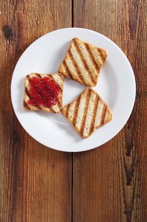 Grilled toasted bread with jam in plate on the table, top view