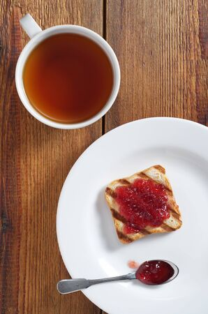 Cup of tea and small toasted bread with jam in plate on wooden background, top view