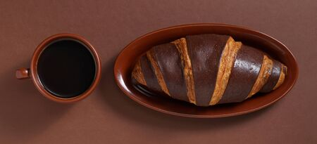 Cup of coffee and chocolate croissant on a brown background, top view Foto de archivo - 135489580