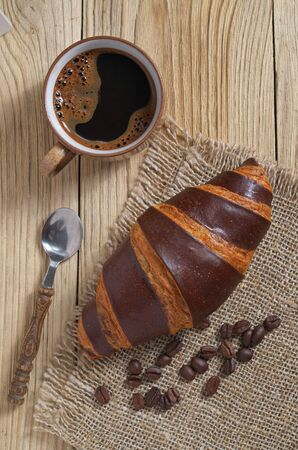 Cup of coffee and chocolate croissant on a wooden background, top view Foto de archivo - 135489688