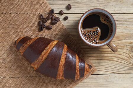Croissant with chocolate and cup of coffee on a wooden background, top view Foto de archivo - 135489689