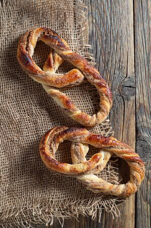 Fresh appetizing pretzels with sugar arranged on over old wooden surface with burlap