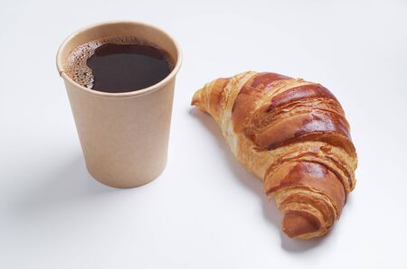 Croissant and paper disposable cup with coffee on white background. Biodegradable dishes