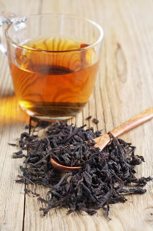 Cup of tea with dried large leaves on a wooden surface. Diet and healthy drink Stock Photo