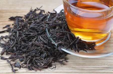 Cup of tea with dried large leaves on a wooden surface. Diet and healthy drink