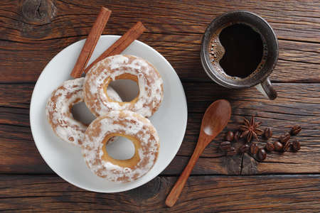 Glazed bagels and cup of coffee on wooden background, top view