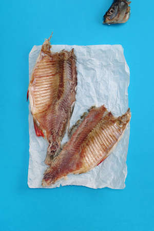 Salted-dried rudd fish on crumpled paper located on blue background, top view