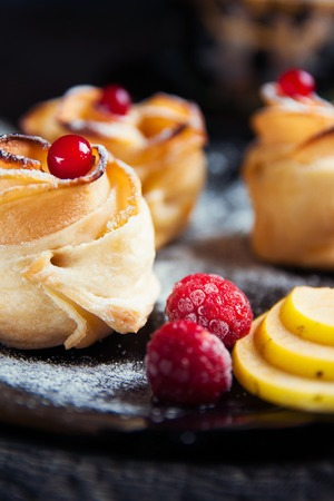 white backing: Fresh puff pastry with apple shaped roses with raspberry, black rowan, cranberry, apple on back plate on white wooden table. Delicious and beautiful apple rose puff pastries Stock Photo