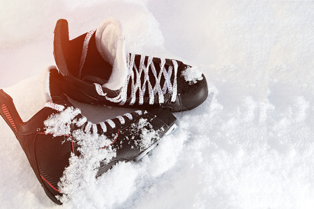 black hockey skates lying in the snow and bright sun. leather, blade, cover, glare Stock Photo