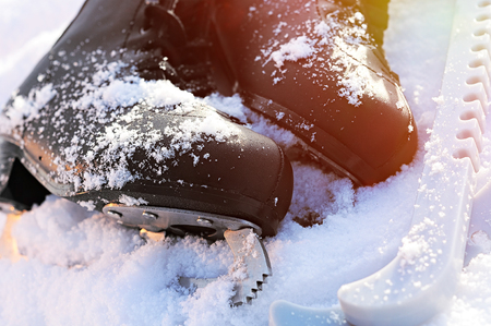 black figure skates lying in the snow and the bright sun. leather, blade, cover, glare Reklamní fotografie