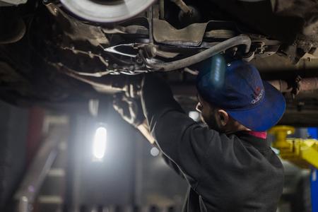 Young caucasian man repairing car with professional tools