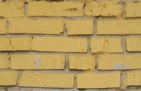 Tiled old painted yellow brick wall background in Kyiv, Ukraine