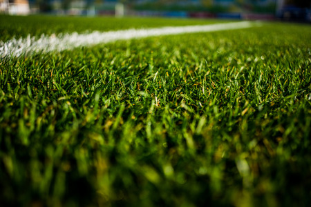 Green bright colorful grass pitch of football stafium, close up with beautiful bokeh and stripes Stock Photo