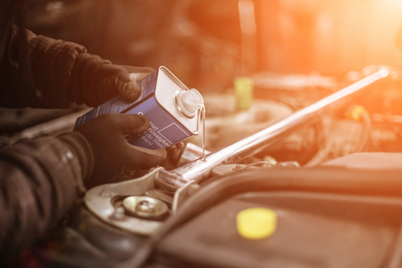Brake DOT4 fluid change up in a car from stylish metal bottle and sunset colors