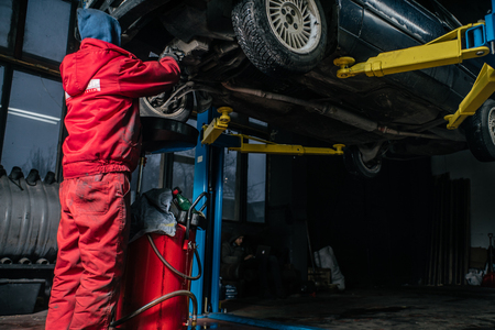 Young caucasian man in red work clothing repairing car with professional tools Stock Photo
