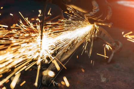 Proffecional worker repair car part with angle grinder. Many sparks on background.