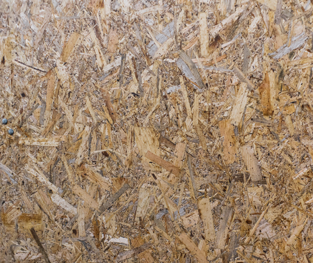 OSB boards are made of brown wood chips sanded into a wooden background. Top view of OSB wood veneer background