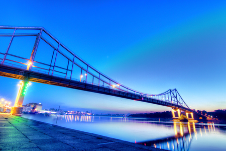 Pedestrian bridge in Kyiv, shoted in dusk illuminated with different colors