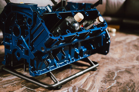 V8 Engine block table, painted in blue color. Loft stylish table furniture with tempered glass