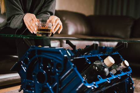 Young caucasian blonde girl sitting on sofa with glass of whiskey at luxury interior with custom v8  car engine table. Fashion picture and beautiful smile