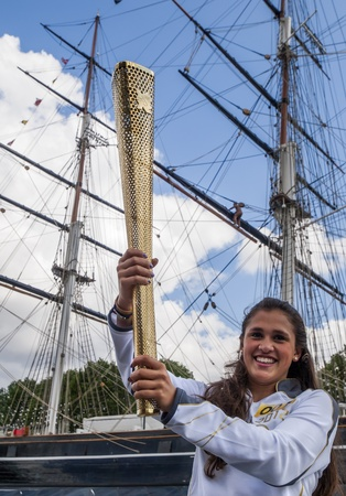 olympiad: 2012 Olympic Games in London. Torchbearer Natasha Sinha holds the Olympic Torch in Greenwich , in front of the clipper ship Cutty Sark