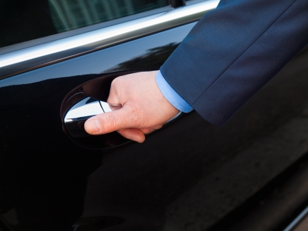 selling service: Chauffeur s hand opening passenger door  Stock Photo
