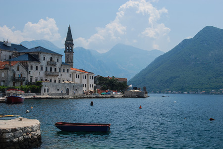 A picturesque view of Perast, an old town on the Bay of Kototr in Montenegro. The photo shows the one of the most beautiful mediterranean towns in baroque-style. The St. Nicholas Church, the Mediterranean sea and surrounding mountains just add an attractiveness to this photo.