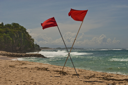 Red crossed flags on the ocean coast warn of the danger to swim in this place. Waves are rather for surfers than for swimmers.