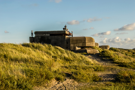 Six teenagers explore a german bunker, built at the time of Second World War, located in the dunes near IJmuiden, the Netherlands. Фото со стока