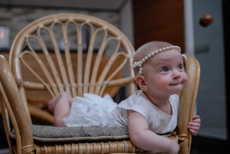A portrait of a five-month baby girl with clear blue eyes in a white dress and pearly headband. The child lies on a rattan chair.