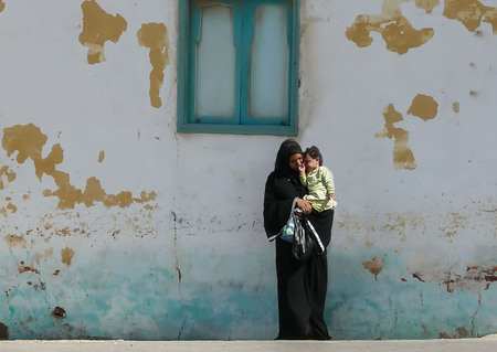 A young mother in a black abaya and hijab stands near an old, dirty and shabby wall, holding in her hands little child. The baby cries and the woman says something to calm him. The photo made in Egypt Фото со стока